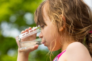 Young caucasian girl drinking from glass with fresh water outdoors during summer time.